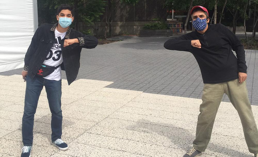 Dean Khurana and student standing far apart with masks