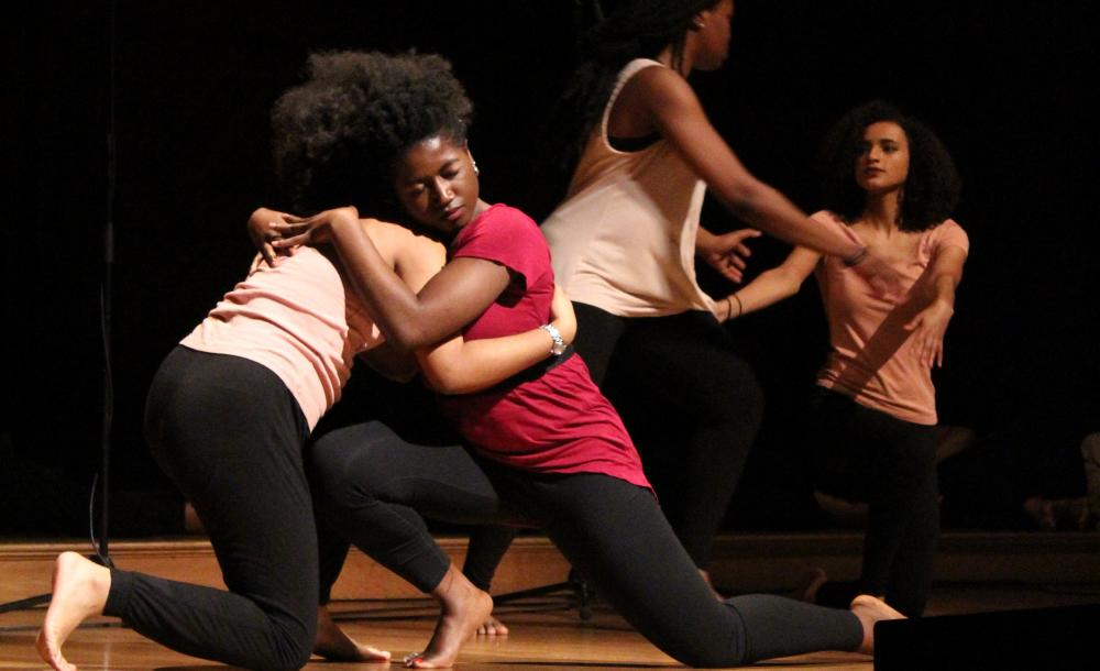 This image shows 4 dancers embracing each other at last year's Kuumba Winter Concert.