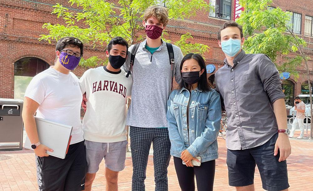 4 male students and one female student in Harvard square wearing masks