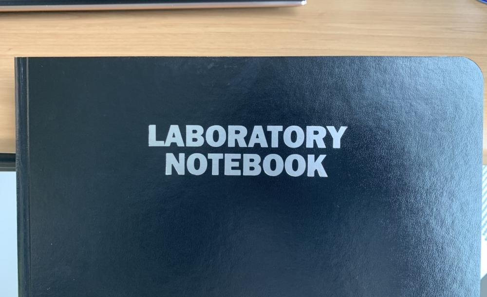 """A black notebook with the words """"LABORATORY NOTEBOOK"""" in white at the center."""