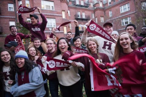 Students cheering with Harvard gear