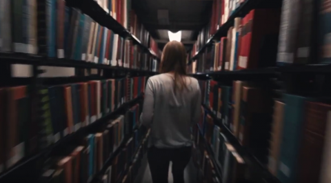 Student walking through library stacks