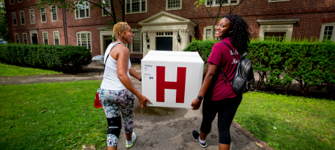 A student and her mother carry a box into a dorm for first-year move-in day
