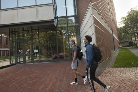 2 students walking on campus wearing masks