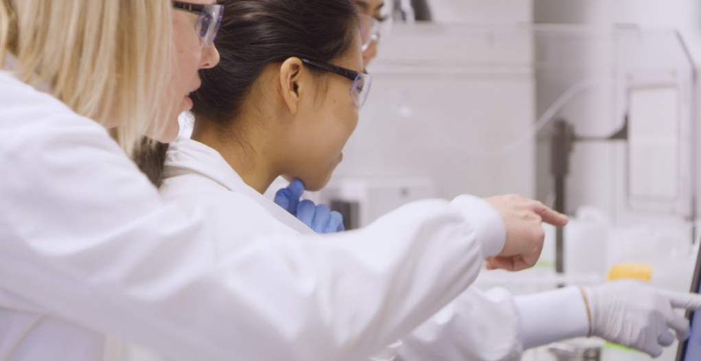 A professor and two students in white lab coats doing research in a lab