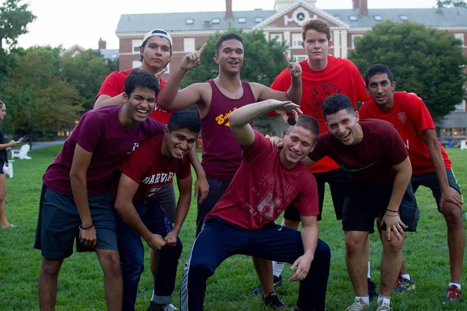students pose in group to celebrate victory on field with team