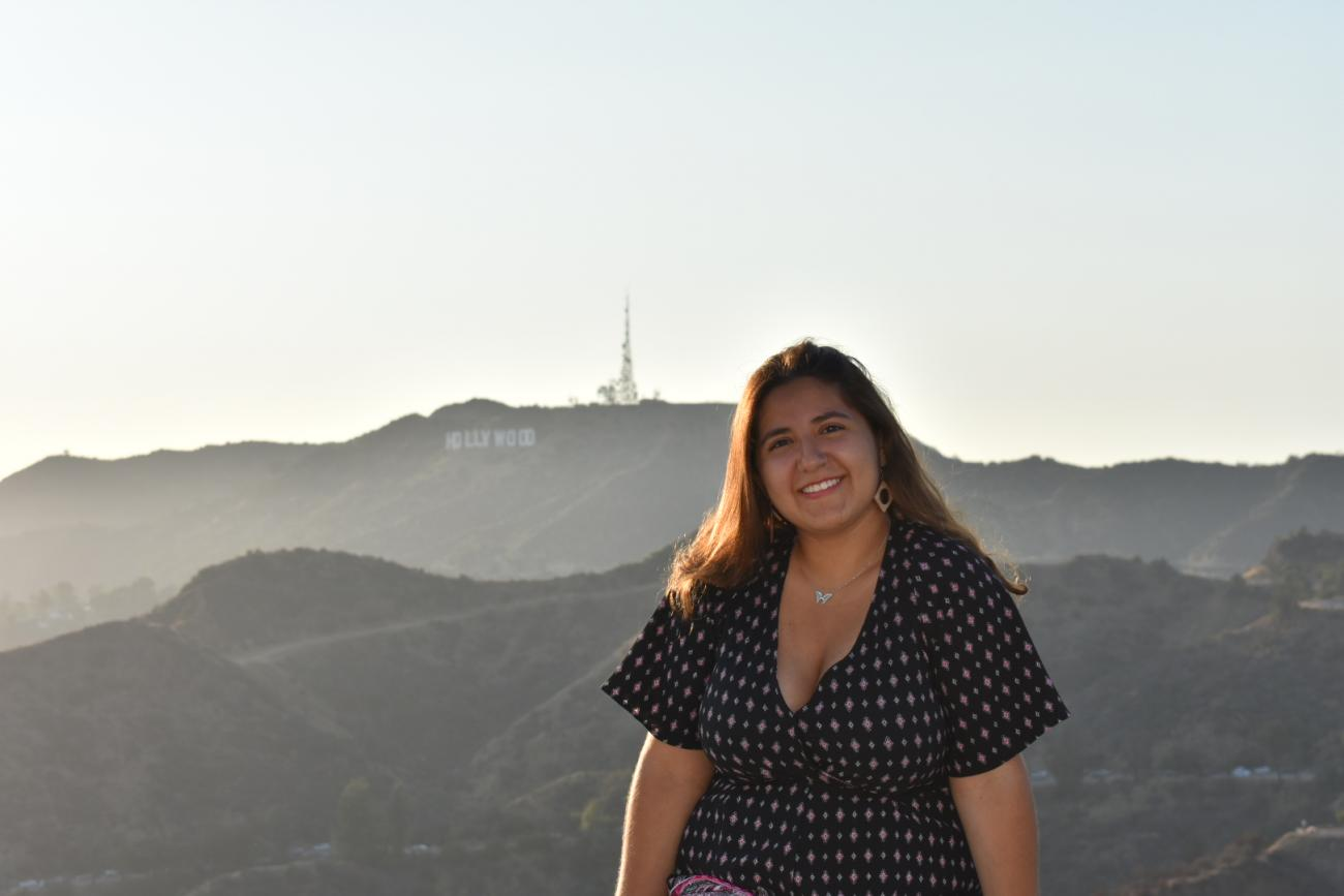 a student in front of Hollywood sign