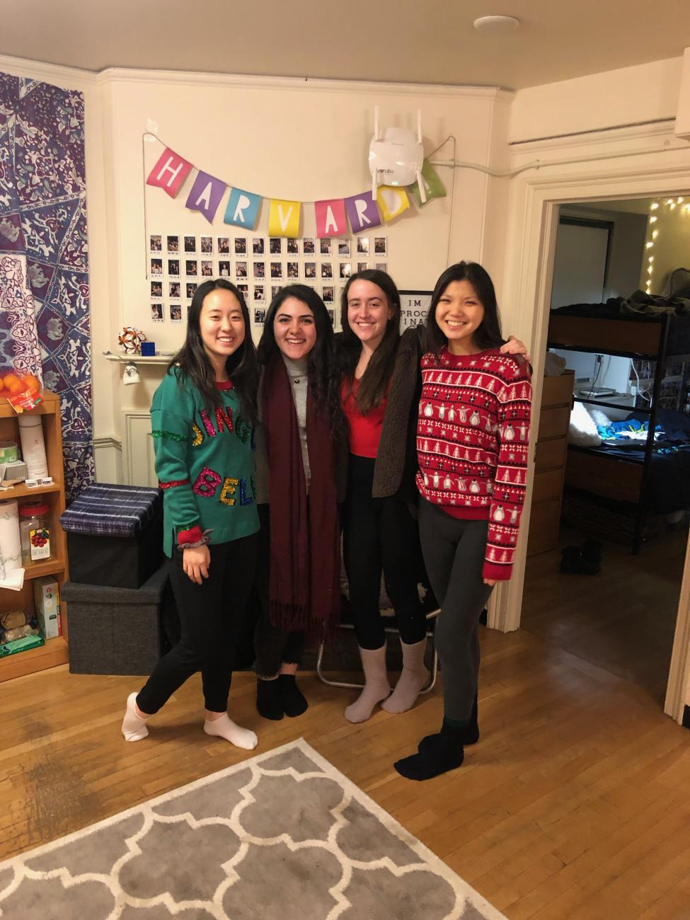 four students pose in dorm room