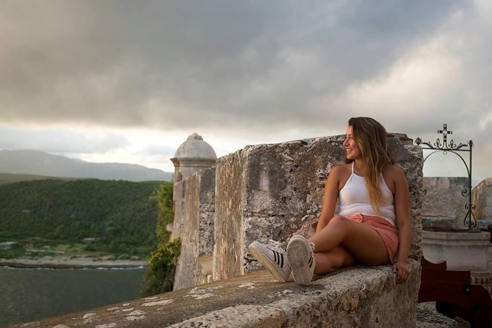 Student sitting on a ledge of a fortress in eastern Cuba