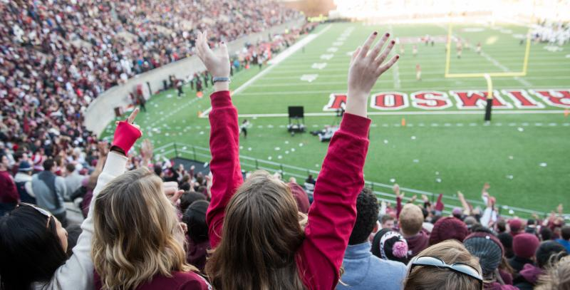 Students cheering at a Harvard football game