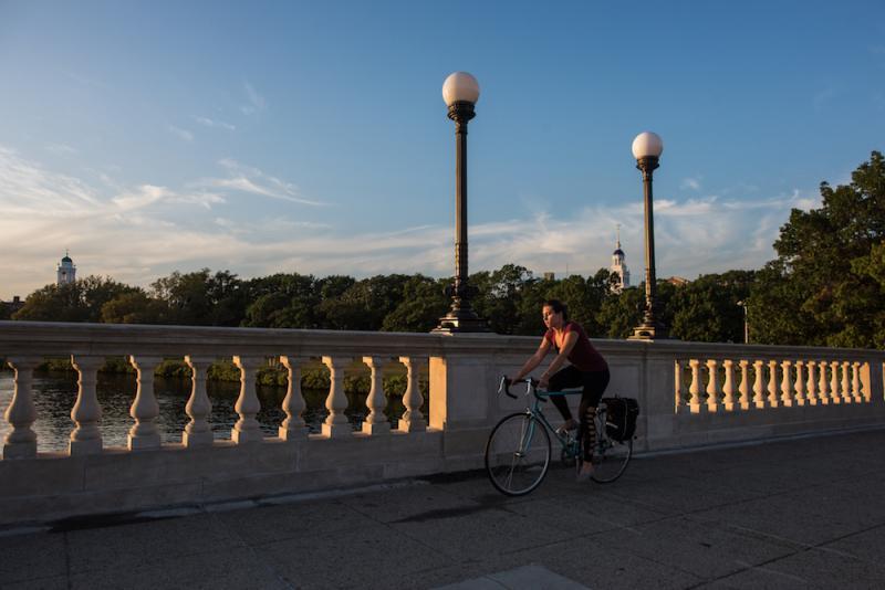 Student biking across bridge