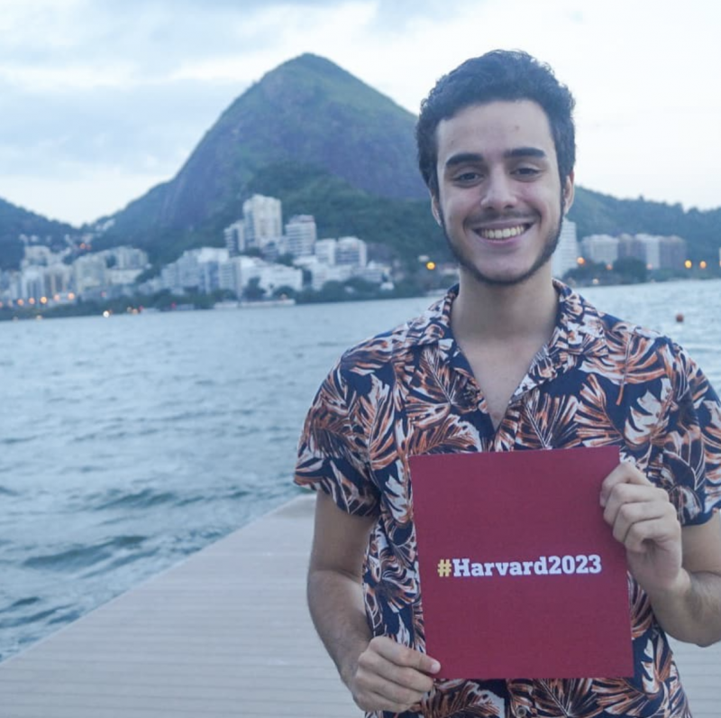 Student posing with #Harvard2023 sign in Rio de Janeiro, Brazil