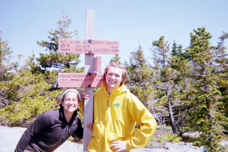 Two people in front of hiking sign