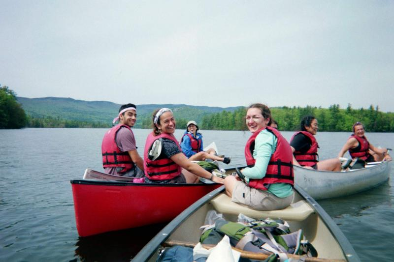Hiking group canoeing on a body of water