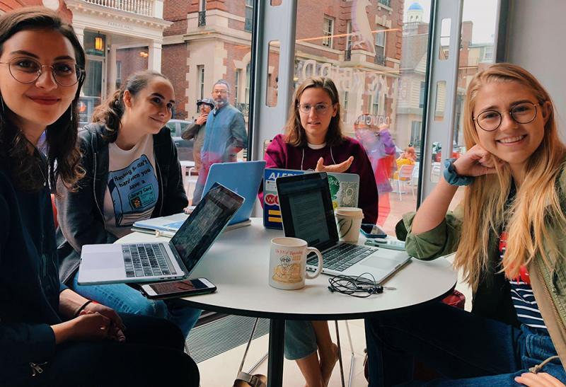 4 female students at a table on their laptops