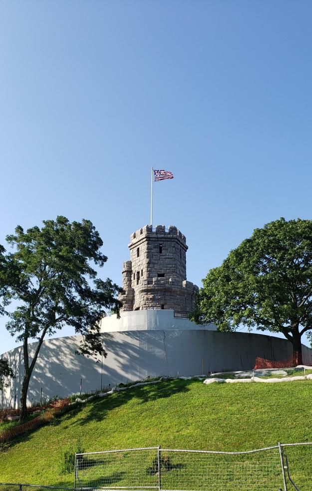 tower with flag flying, on a grassy hill with trees