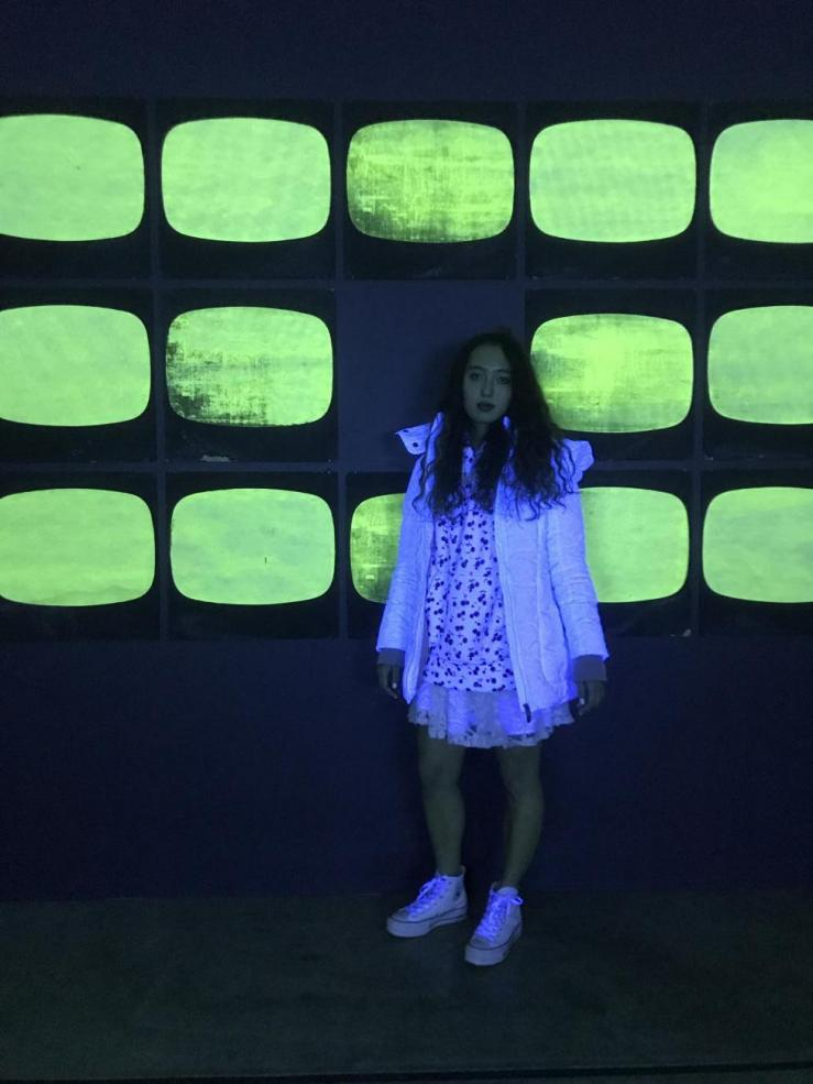 Alian standing in front of her art project - a neon green wall lit up by blacklights