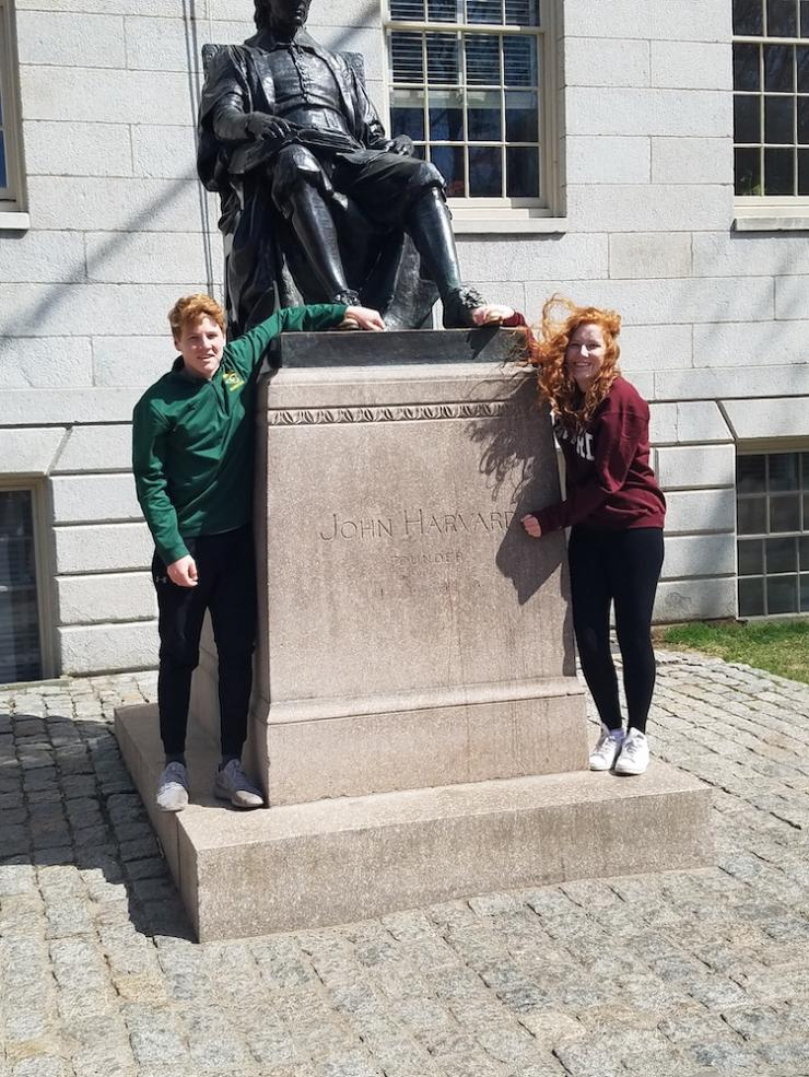Allison and her brother posing with the John Harvard Statue