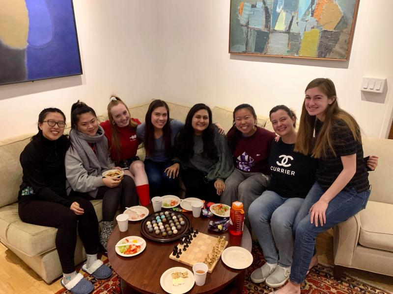 Maria posing with seven of her friends in Currier House, one of the upperclassmen dorms.