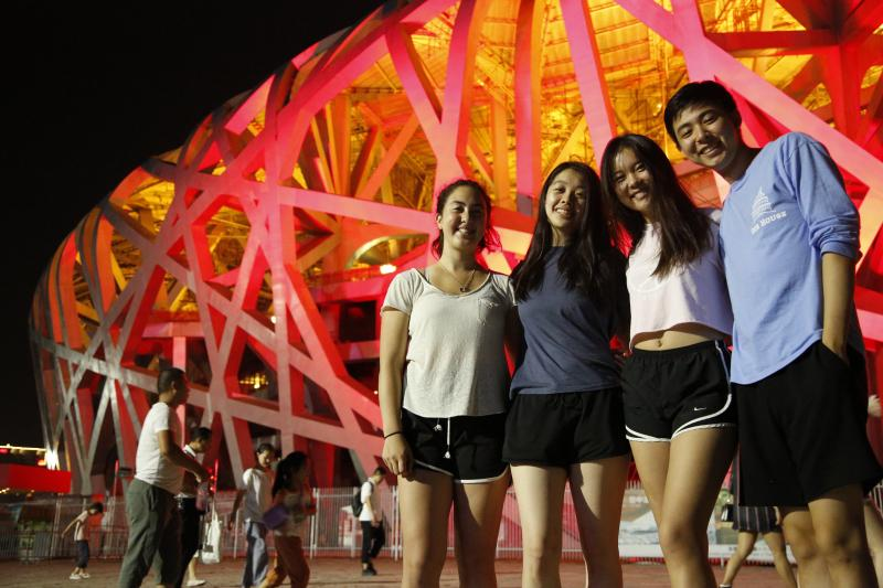 Four people standing in front of the Olympic Stadium in Beijing