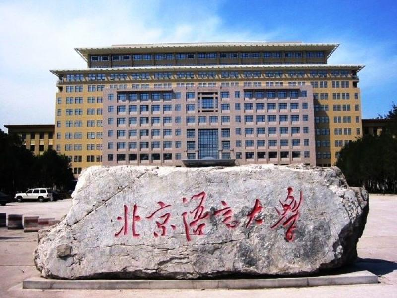 Stone with chinese characters in front of large classroom building