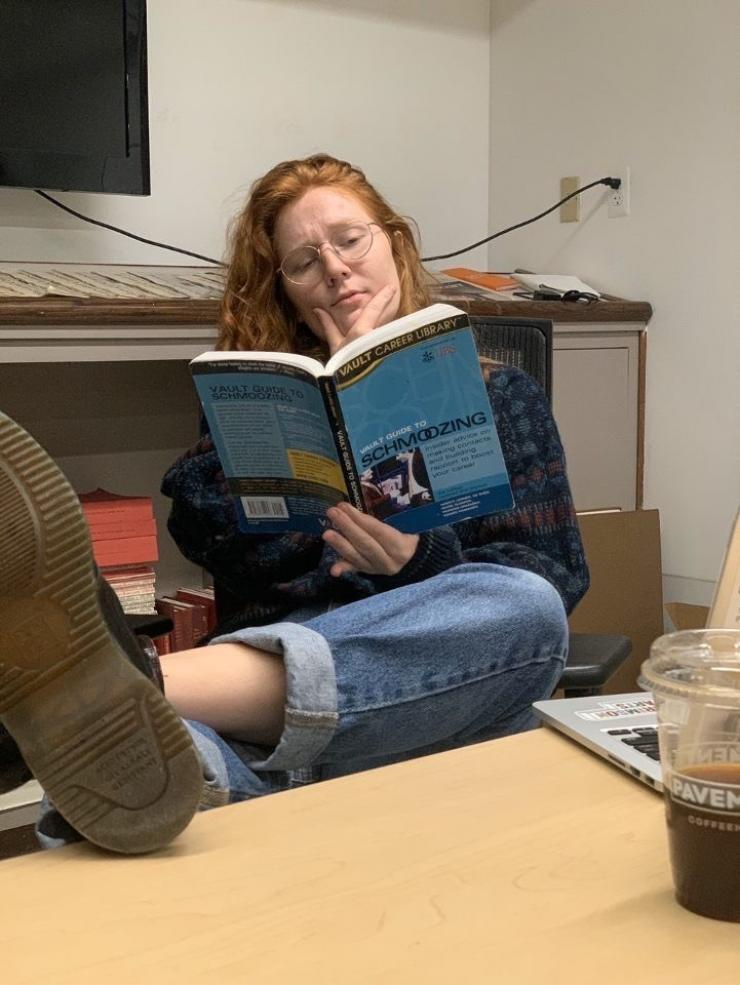"""me holding a book titled """"schmoozing"""" with my feet up on a table in the building of The Harvard Crimson"""