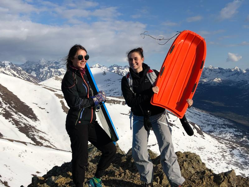 Two girls holding sleds on a mountaintop