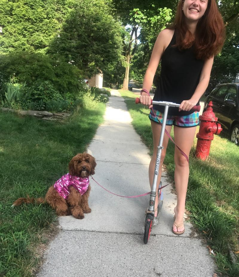 Girl riding scooter with dog next to her