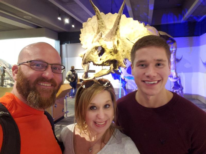 Family posing in front of dinosaur fossil
