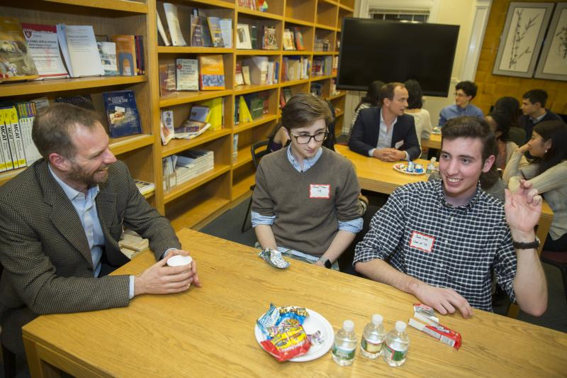 Music professor, Alex Rehding, (from left) talks with Jake Tilton '19 and Jacob Link '19 inside the Office for Career Services during a dinner with arts and humanities faculty and students.