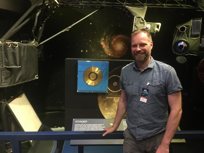 """Professor Alexander Rehding stands next to the Golden Record, the subject of his General Education Course """"Music from Earth."""""""