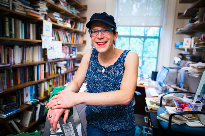 Professor Stephanie Burt poses in her office, surrounded by books.
