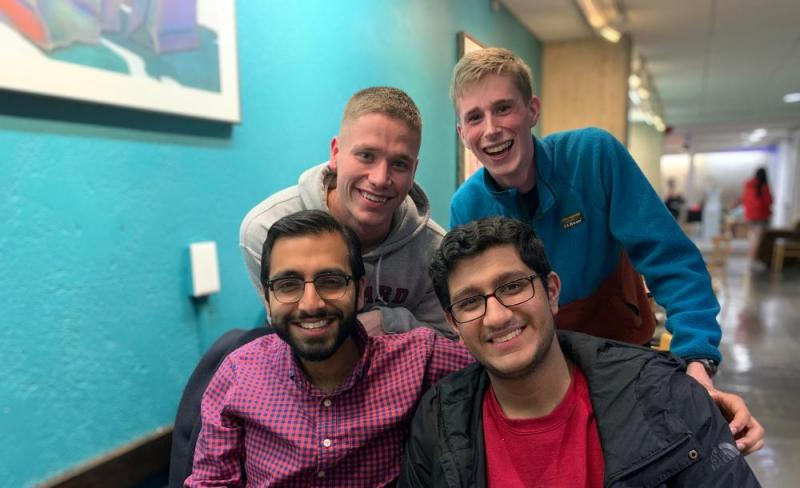 A group of four students smiling together