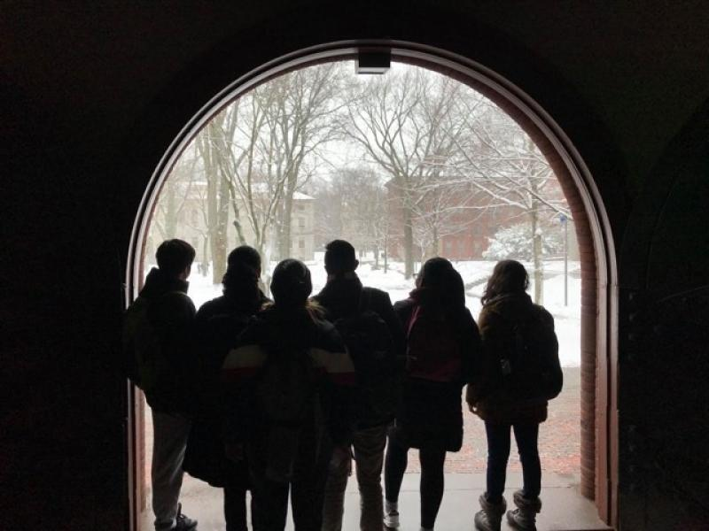 A group of students standing at a doorway looking at snow
