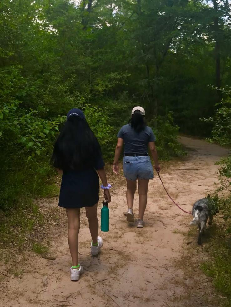 Two girls hiking along a path.