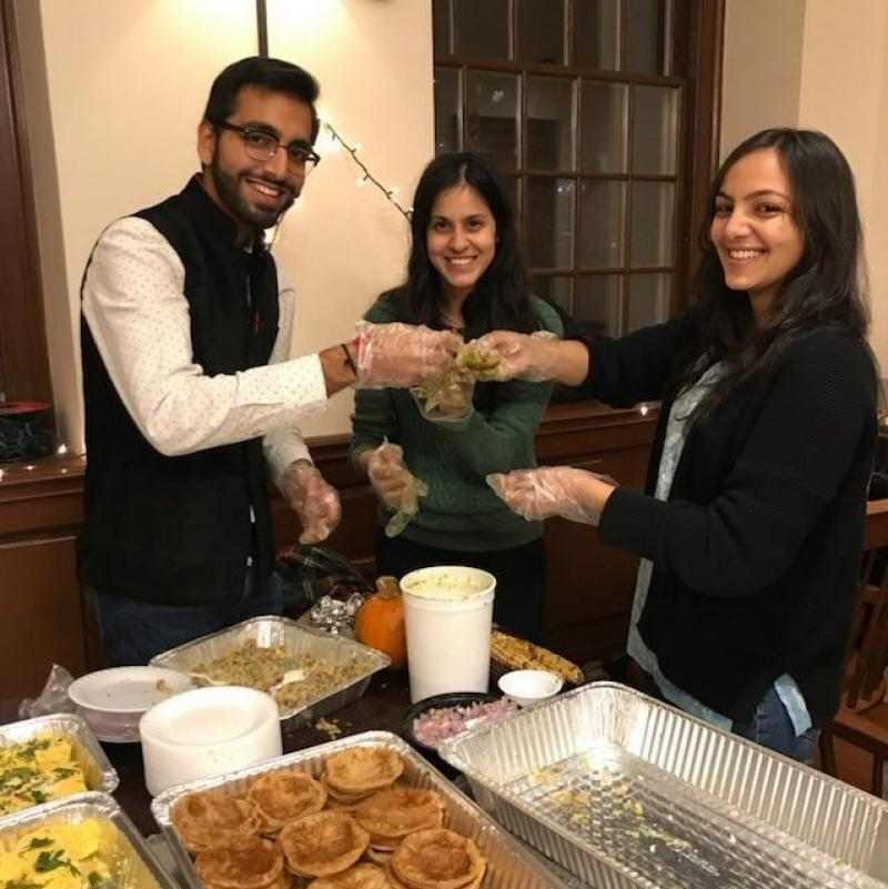 Three college students indoors holding up Indian food