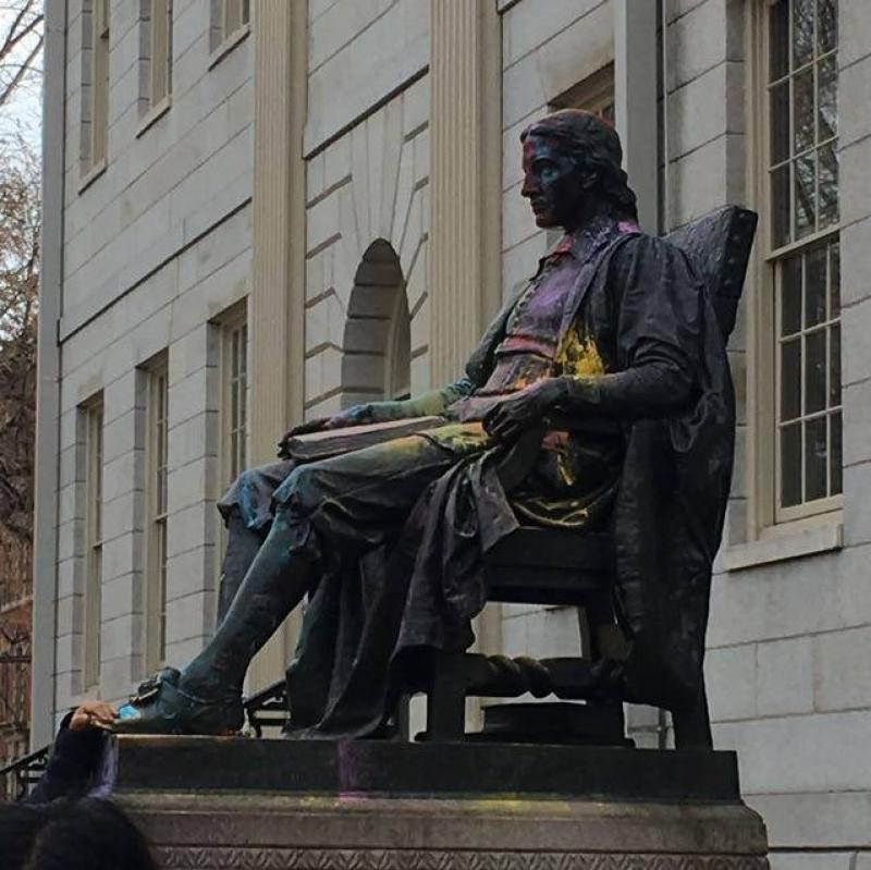 Statue of John Harvard lightly dusted with colored powder