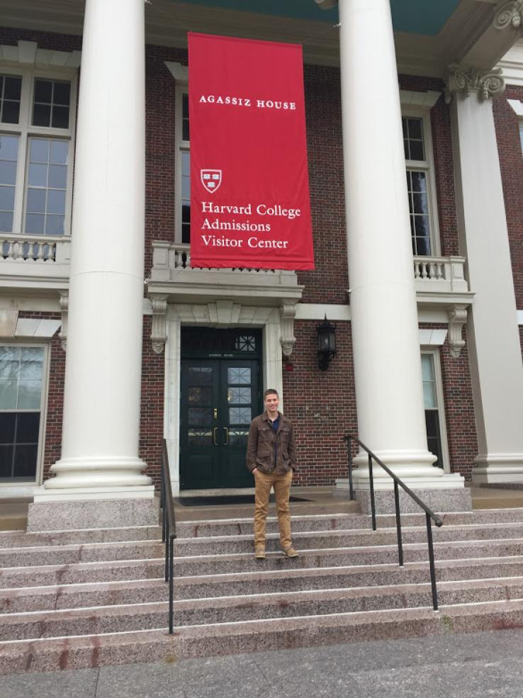 A student posing in front of the Harvard Visitors' Center