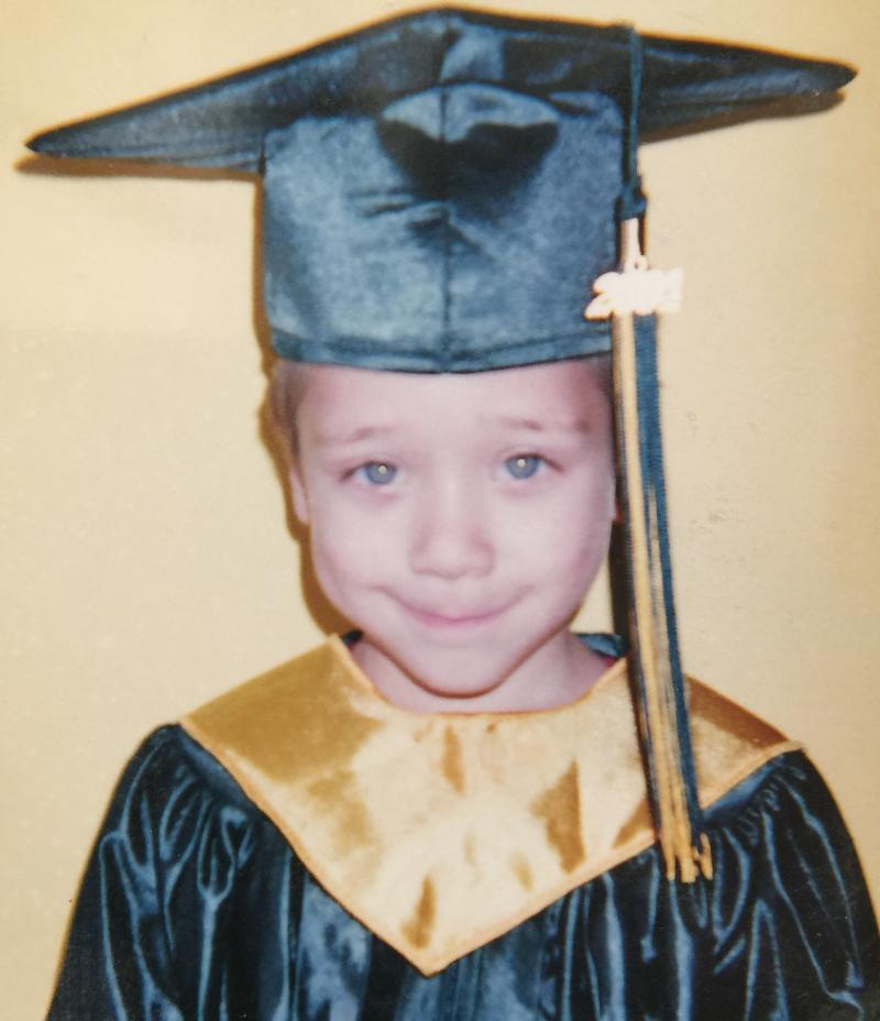 Young child posing for Kindergarten graduation