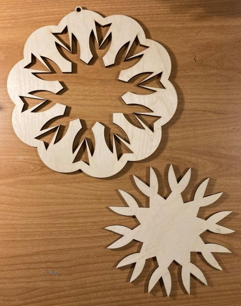 Two woodcut designs in the shape of snowflakes