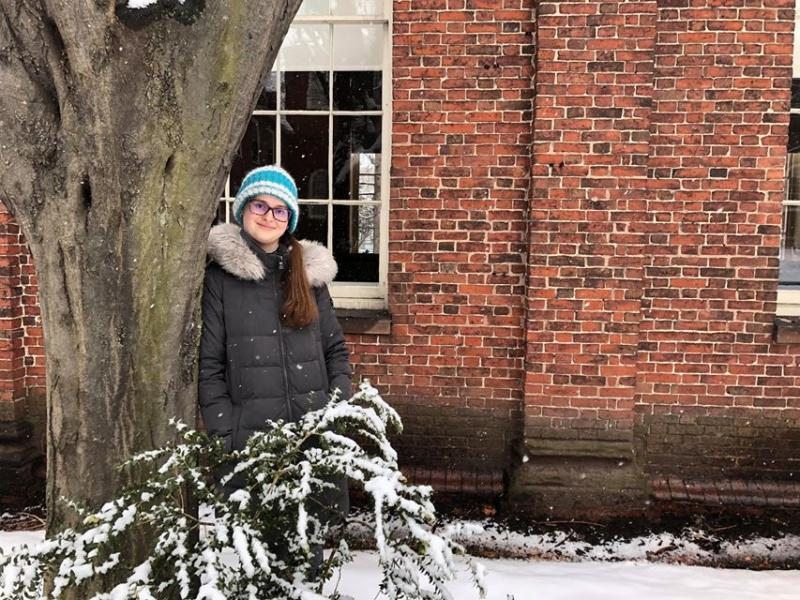 A photo of a girl wearing a gray coat and green beanie, leaning against a tree on a snowy day