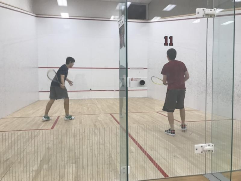Two students playing squash