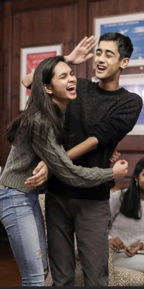 Siona Prasad in green sweater hugging Nikhil Dharmaraj in black sweater, with his hand raised