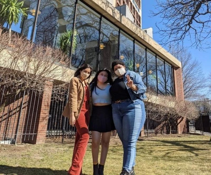 Three girls standing outside a building.