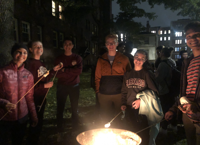 Students roasting marshmallows around a fire
