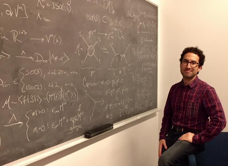 Preceptor Camille Gomez-Laberge stands in front of a chalkboard in his office.