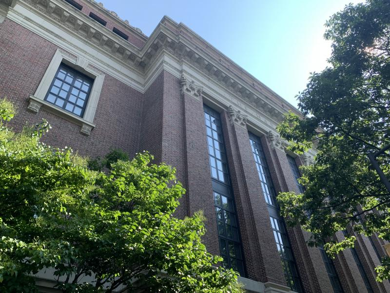 The back of Widener Library on a sunny day surrounded by trees