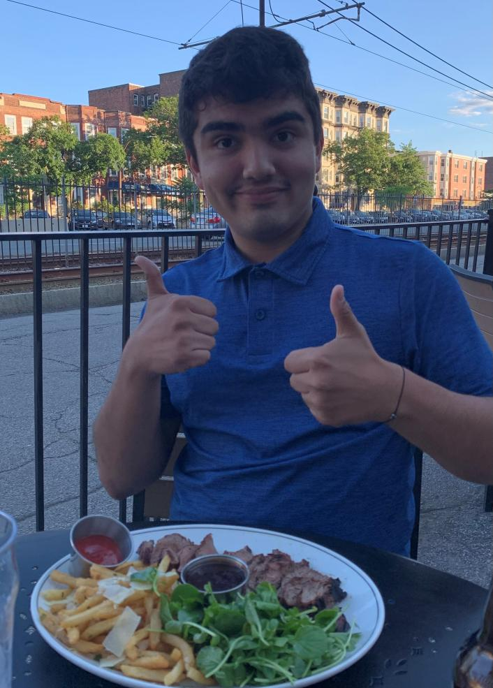 A man showing thumbs up and eating food outside.