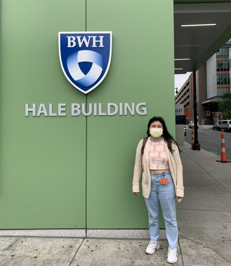 """A girl standing outside a building wall that says """"BWH Hale Building."""""""