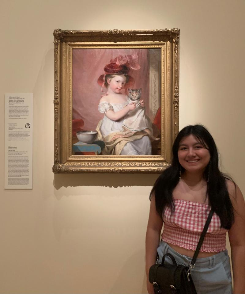 A girl standing in front of an painting of a young girl holding a cat.